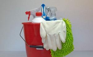 Bildinhalt: Ein Roter Eimer mit zwei Reinigungsmittel zum sprühen, zwei weiße Gummi Handschuhe, ein grüner Putzlappen, ein Reinigungsmittel